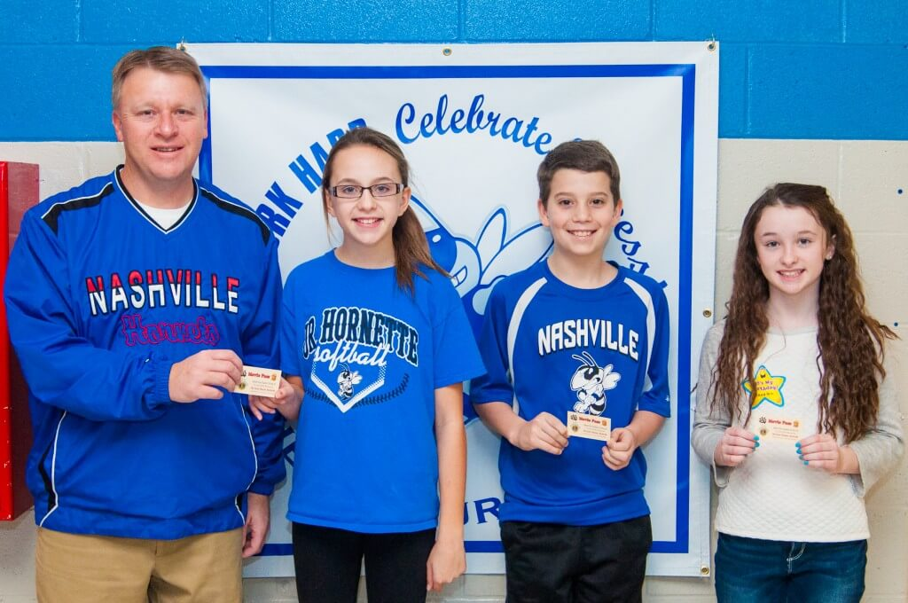 Nashville Primary School Superintendent and Nashville Lions Club member Michael Brink gives State Theater movie tickets to Kiley Heidel, Jonah Kemp and Havalen Pierce.